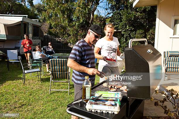 Family cooking barbeque in back garden.