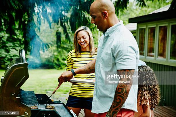 Family cooking burgers on barbecue in backyard
