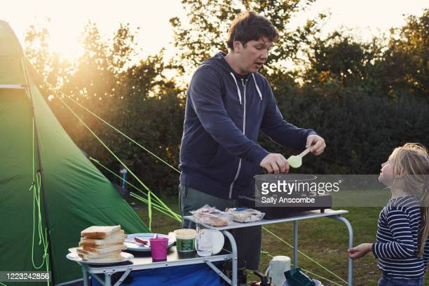 family cooking dinner outdoors on a camping holiday - tent stock pictures, royalty-free photos & images