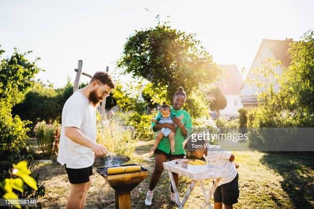 family cooking food on bbq in back garden - carrying stock pictures, royalty-free photos & images