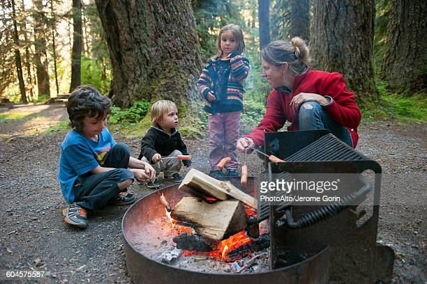 Family cooking hotdogs over campfire