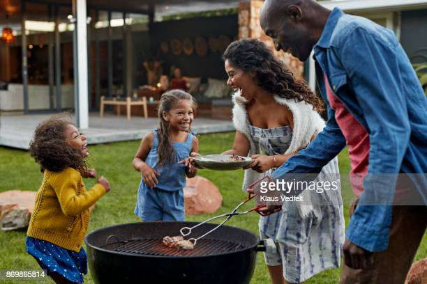 family cooking on grill in their garden - barbecue social gathering stock pictures, royalty-free photos & images