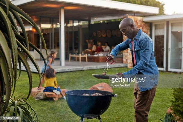 family cooking on grill in their garden - grelhado cozido - fotografias e filmes do acervo