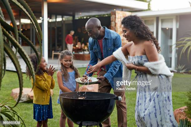 Family cooking on grill in their garden