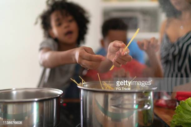 family cooking together at kitchen - pasta stock pictures, royalty-free photos & images
