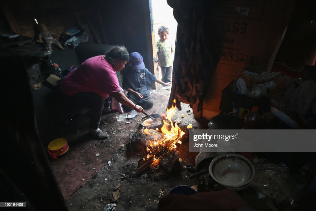 A family cooks a plate of beans and cheese in their modest home inside the Tirabichi garbage dump on March 5, 2013 in Nogales, Mexico. About 30 families live at the landfill, searching for recyclables to sell for a living. Some are formerly undocumented workers deported back to Mexico to the United States. Many have received protective work gloves from the nearby non-profit Home of Hope and Peace, which plans to further expand its assistance to Tirabichi residents.