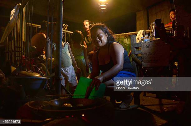TACLOBAN LEYTE PHILIPPINES DECEMBER 24 A family cooks Noche Buena or Christmas meal in their damaged house on Christmas eve on December 24 2013 in...