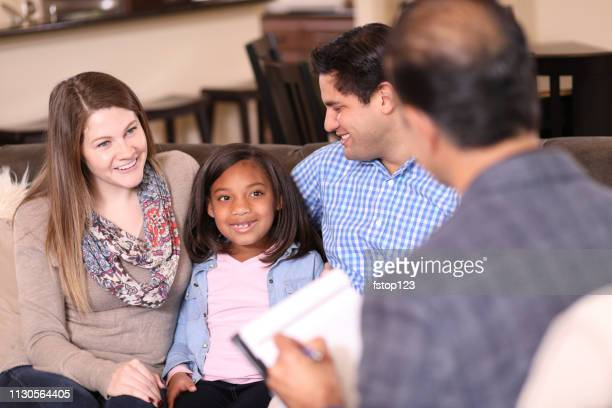 Family counseling session at home with therapist.