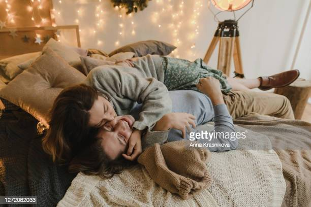 family couple lying on bed at christmas - time stock pictures, royalty-free photos & images