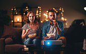 Family couple watching television projector at home on sofa