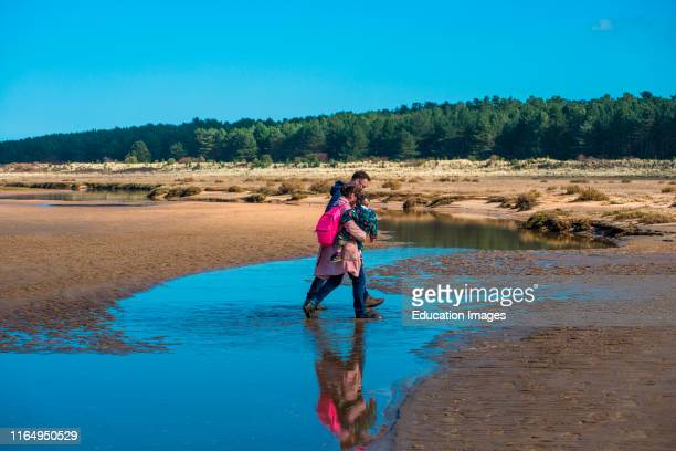 A family cross water pools left by the tide on sandy beach at Holkham bay North Norfolk coast East Anglia England UK