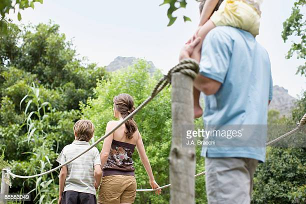 Family crossing footbridge in remote area