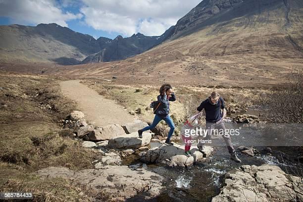 Family crossing stream, Fairy Pools, Isle of Skye, Hebrides, Scotland