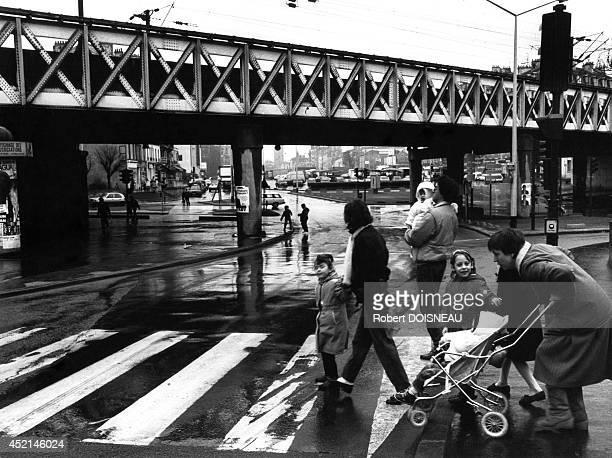 A family crossing the street on a crosswalk avenue du President Wilson 1987 in SaintDenis France