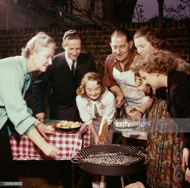 A family crowd round a charcoal barbeque as a man prepares to cook steaks and sausages on the hot coals in the back garden of a house in England in...