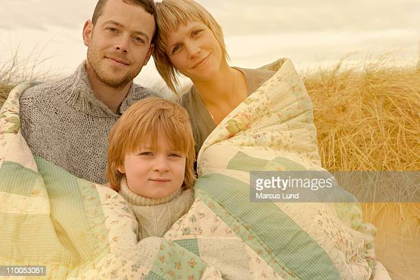 Family cuddling under quilt on beach