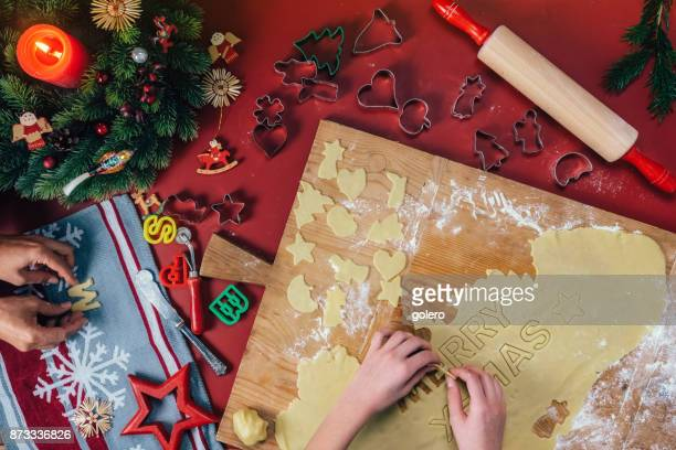 family cutting out christmas cookies on wooden table - fotosession stock photos and pictures
