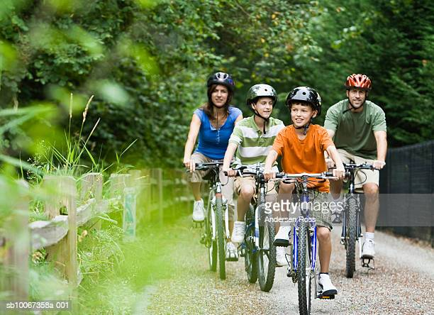 family cycling in park - riding stock pictures, royalty-free photos & images