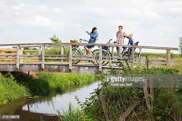 Family cycling over wood bridge