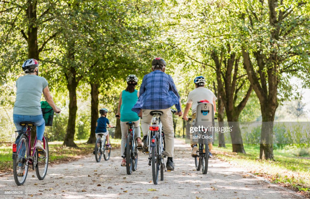 Family Cycling Together Through Park : Stock Photo