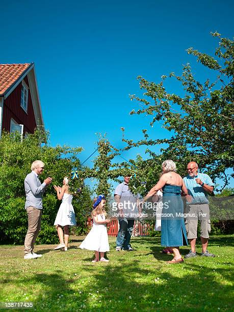 family dancing around maypole in garden - maypole stock pictures, royalty-free photos & images