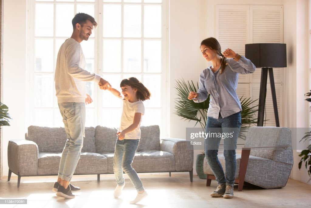Family dancing in living room spending time on weekend together : Stock Photo