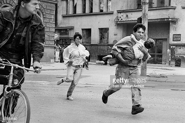 Family dash across 'Sniper Alley' to avoid gunfire during the siege of Sarajevo in 1994.
