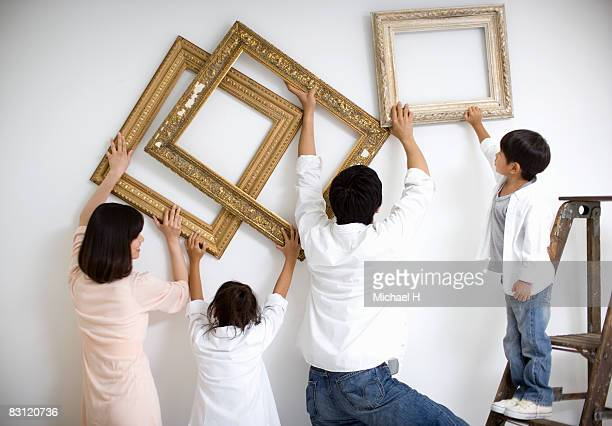 Family decides position of picture frame by wall