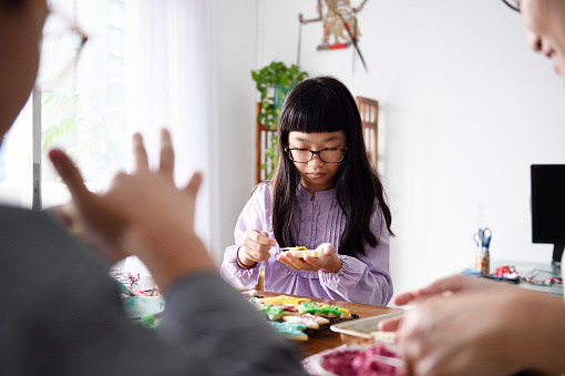 Family decoating sugar cookies together - gettyimageskorea