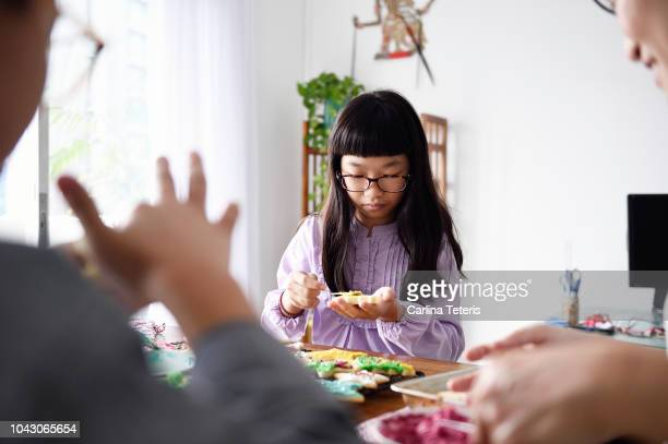 family decoating sugar cookies together - chinese decoration stock pictures, royalty-free photos & images