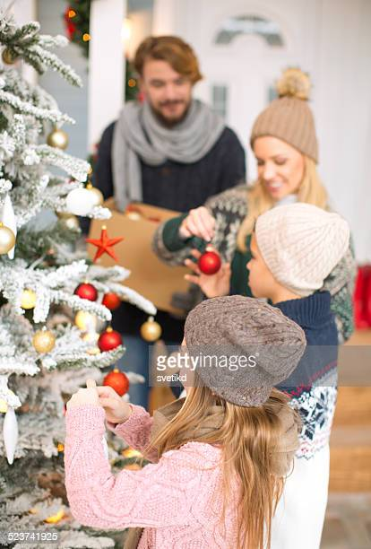 family decorating christmas tree. - decorating stock pictures, royalty-free photos & images