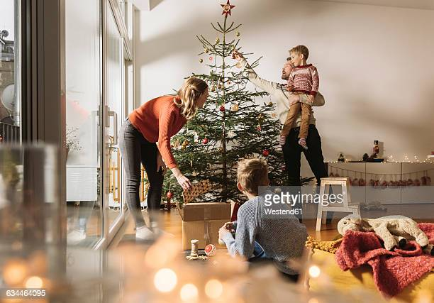 family decorating christmas tree - ornato foto e immagini stock