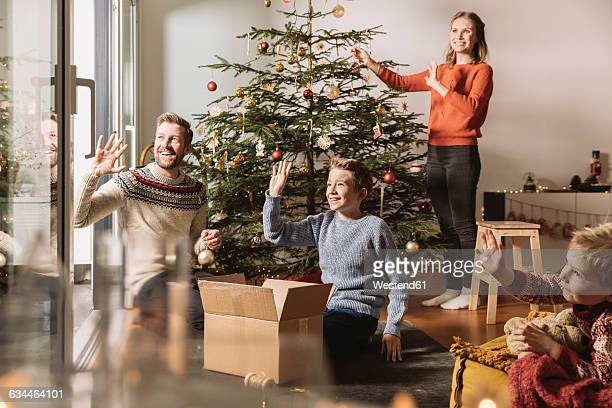 Family decorating Christmas tree, waving out of window