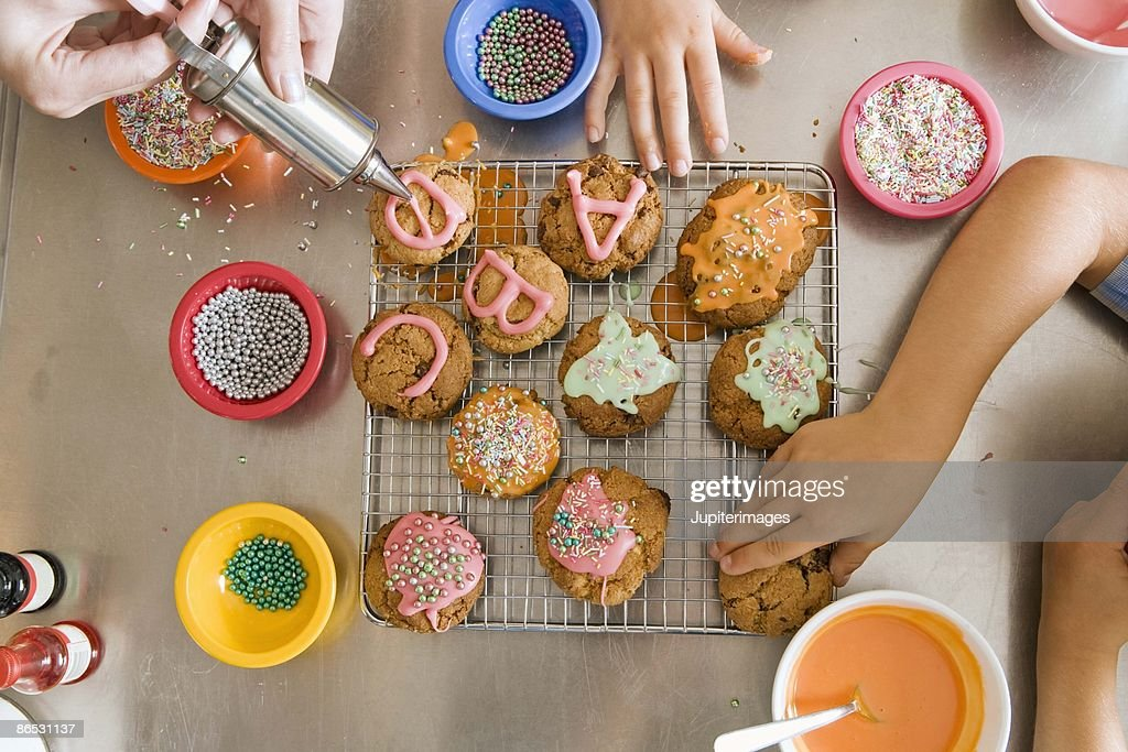 Family decorating cookies : Stock Photo