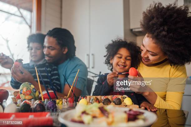 family decorating easter eggs and smiling - african american easter stock photos and pictures