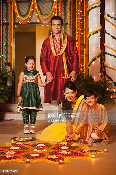 Family decorating rangoli with oil lamps on Diwali