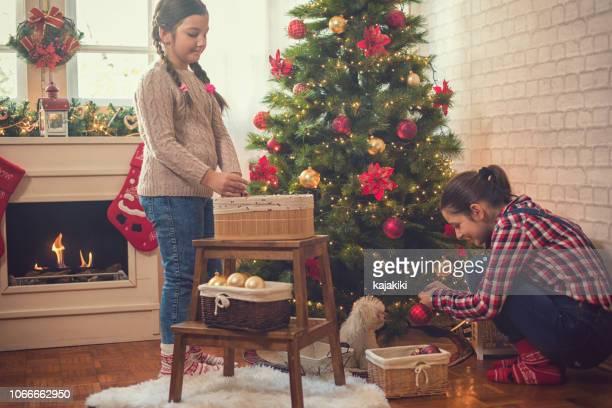 家族が自宅のクリスマス ツリーを飾る