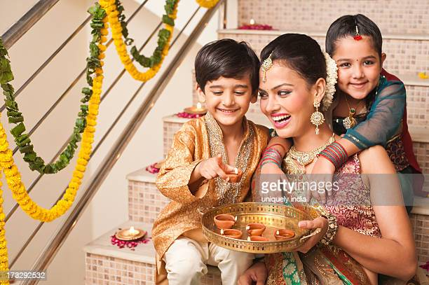 family decorating with oil lamps on diwali - diwali celebration stock photos and pictures