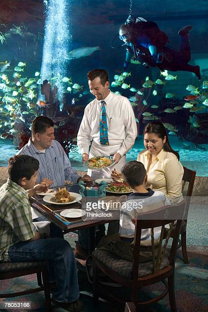 Family dining in restaurant inside public aquarium