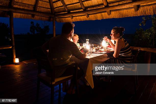 A family dining on the verandah of a luxury safari camp tent.