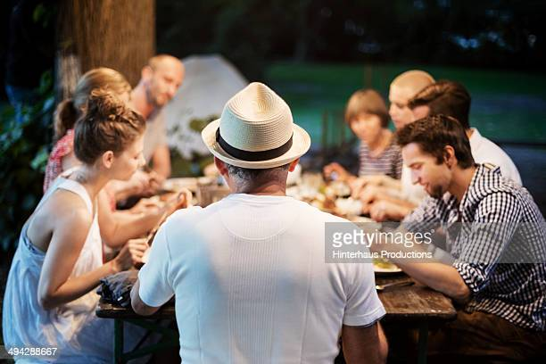 family dinner at the garden - mom sits on sons lap stock pictures, royalty-free photos & images