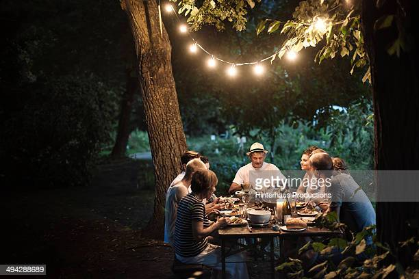family dinner at the garden - lamp stock-fotos und bilder