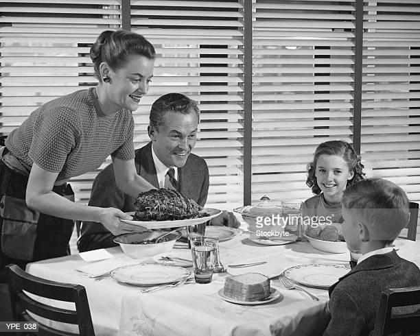Dîner en famille, mère tenant une assiette de rôtis