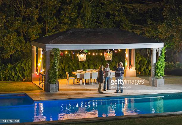 family discussing at gazebo by poolside - gazebo stock pictures, royalty-free photos & images
