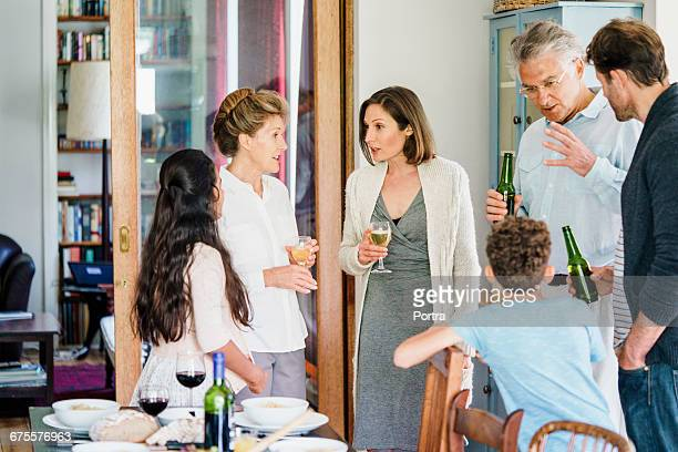 Family discussing while having wine at home