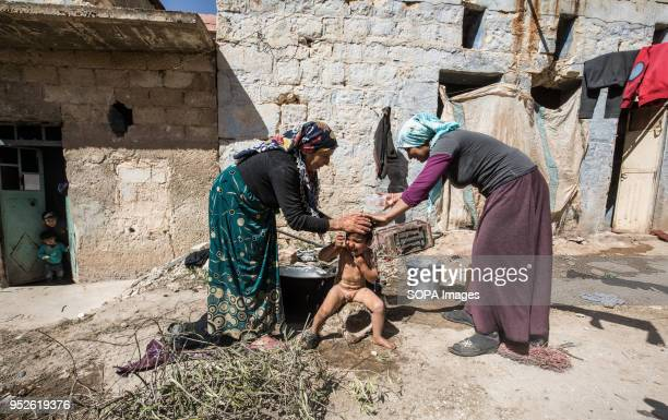 A family displaced from Afrin living in the corner of a destroyed house in Fafin They cook and take a shower outside their new destroyed home An...