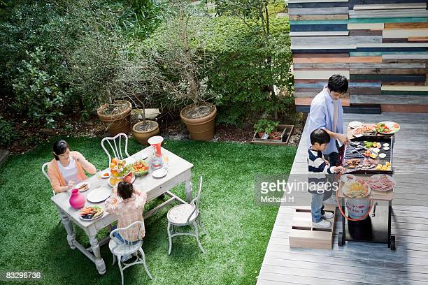 Family do barbecue in garden