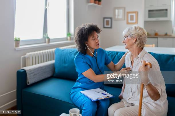 family doctor checking elderly woman with stethoscope - heart internal organ stock pictures, royalty-free photos & images