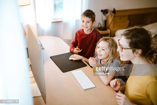familie doet schoollessen thuis en online - mid adult women stockfoto's en -beelden