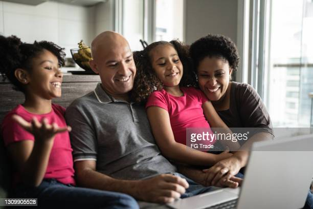family doing a video call on laptop at home - webcam media apparaat stock pictures, royalty-free photos & images